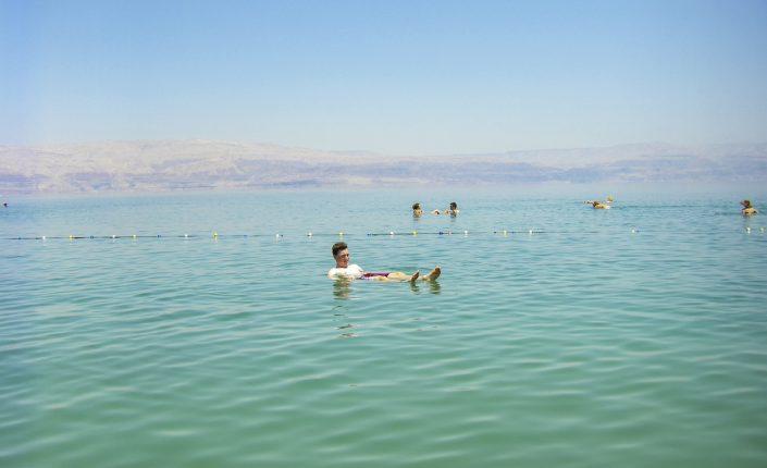 Oameni care plutesc pe apă în Marea Moartă, Israel.